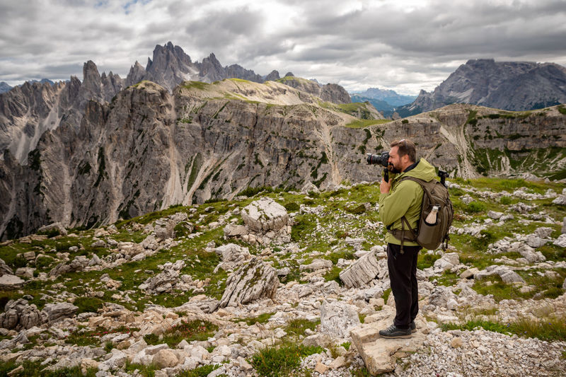 Photographer with telephoto lens in mountain landscape. man with mountain trekking sportswear