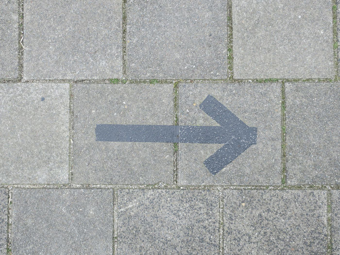 High angle view of arrow sign on footpath