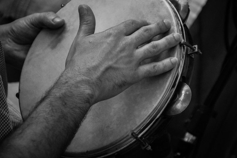 Cropped image of man playing tambourine
