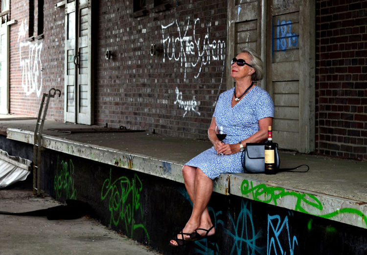 #urbanana: The Urban Playground 65+ Lady Architecture Brick Brick Wall Building Exterior Built Structure Casual Clothing Contrast Day Drinking Wine Emotion Fashion Front View Full Length Graffiti Lifestyles Odd Place One Person Outdoors Real People Sitting Wall EyeEmNewHere