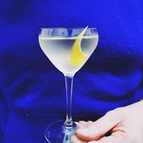 Close-up of hand holding drink against blue glass