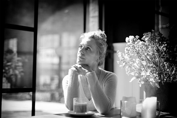 Portrait of woman sitting by window at restaurant