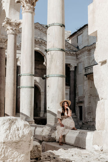 Woman sitting on old building