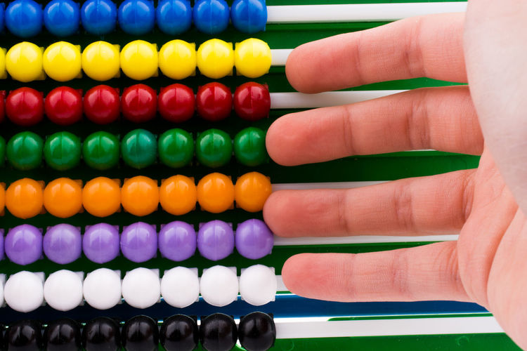 Close-up of hand over multi colored abacus