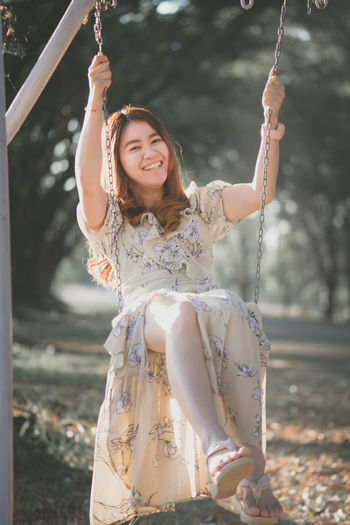 Portrait of smiling young woman on swing at land