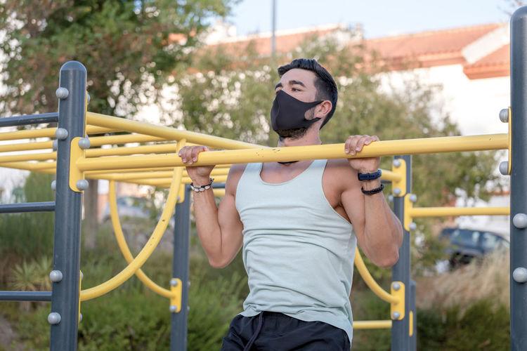 Young man wearing mask exercising at playground