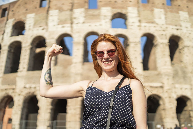 Portrait of smiling mid adult woman against building
