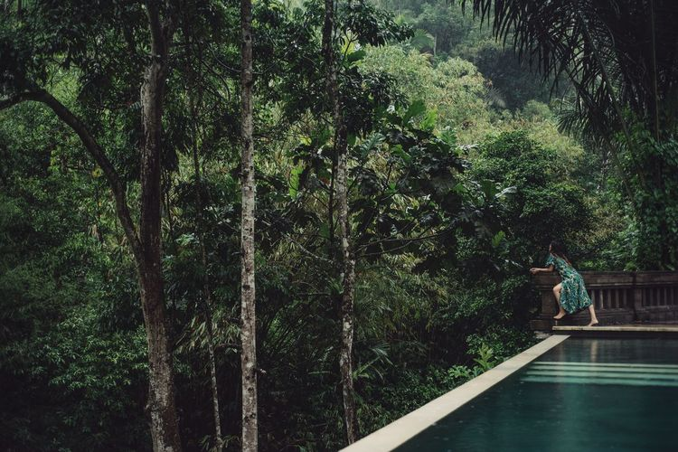 Side view of woman standing by swimming pool and wall against trees