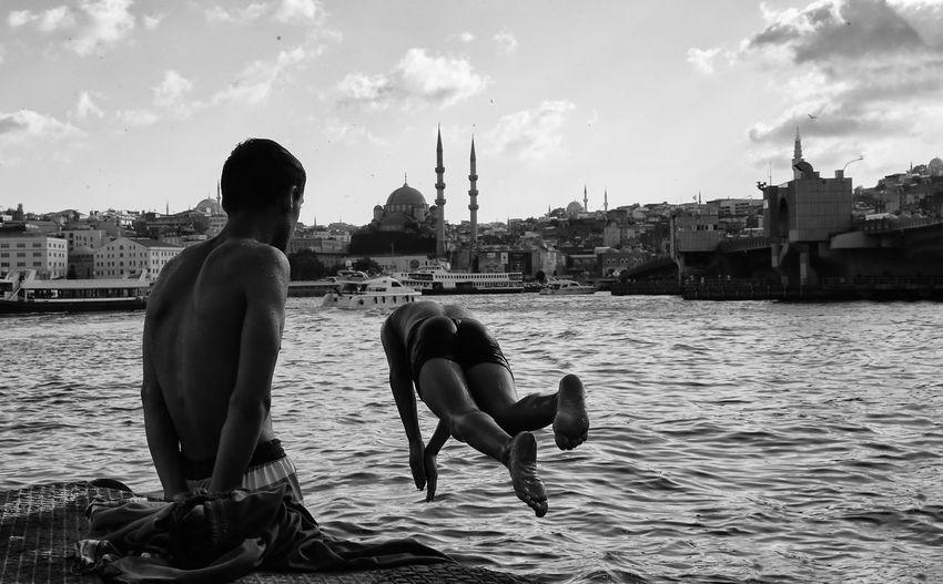 Men on riverbank in city against sky