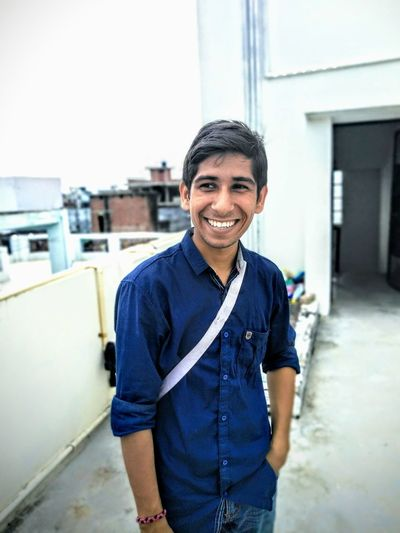 Smiling Young Man Standing On Terrace