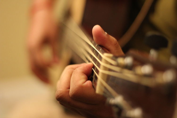 Close-up of person playing acoustic guitar