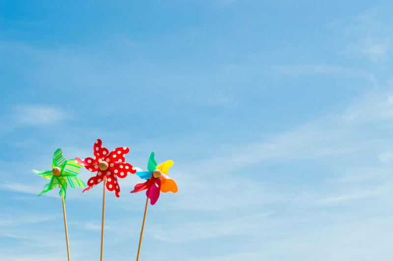 Close-up of colorful pinwheel toys against sky