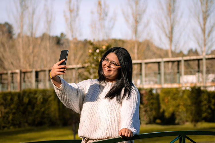 Young woman making selfie with a smartphone at sunset in the park.