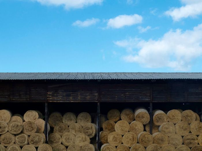 View Of Hay Bales In Barn Against Blue Sky