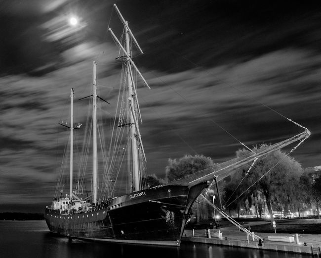 Sailboats moored on river against sky at night