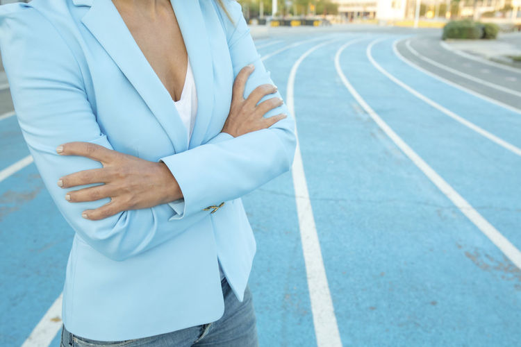 Close up portrait of business woman while standing with arms crossed on a athletics court One Person Midsection Day Sport Hand Real People Standing Lifestyles Focus On Foreground Men Clothing Human Hand Leisure Activity Front View Sports Clothing Road Exercising Healthy Lifestyle Outdoors