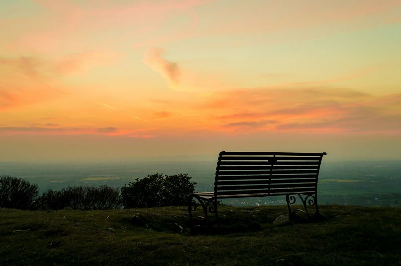 Silhouette Bench On Field Against Cloudy Sky During Sunset