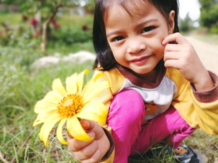 Midsection portrait of cute girl holding yellow flower