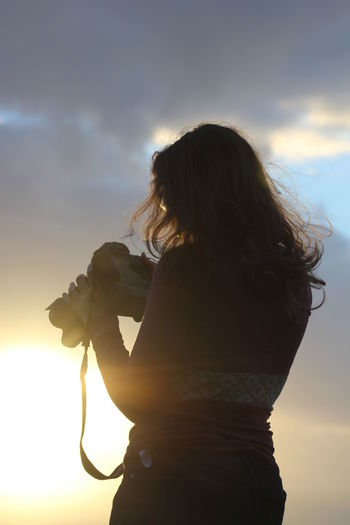 Rear view of woman holding digital video camera while standing against sky during sunset
