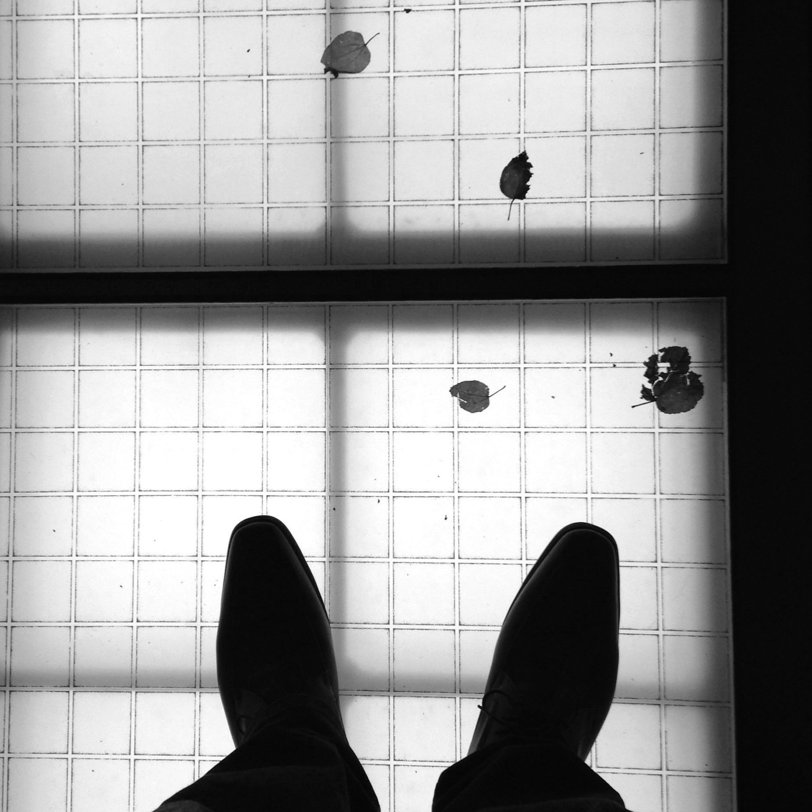 low section, indoors, shoe, person, tiled floor, flooring, footwear, human foot, standing, tile, personal perspective, floor, men, high angle view, unrecognizable person, lifestyles, wall - building feature