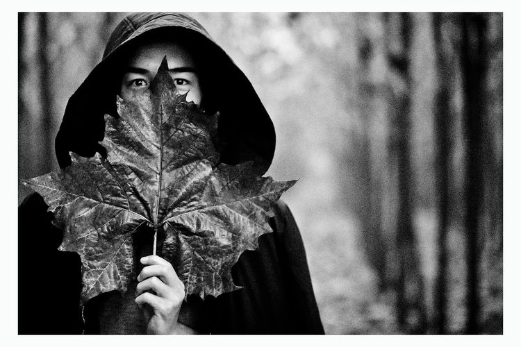 Man Covering Face With Leaf While Standing Outdoors