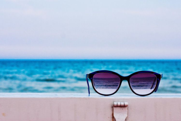 Close-Up Of Sunglasses On Retaining Wall Against Sea