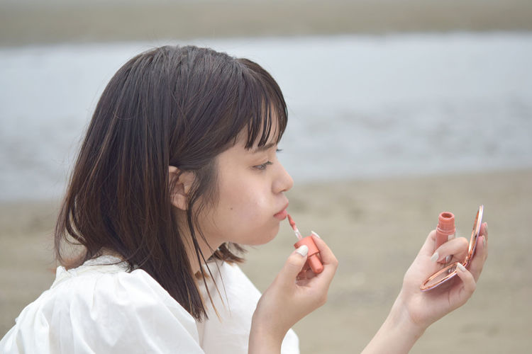 Portrait of young woman holding ice cream against sea