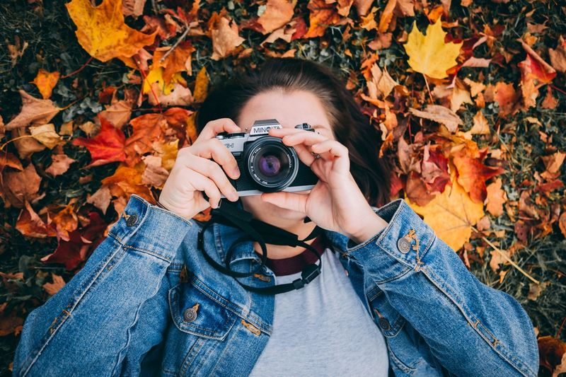 Midsection of woman photographing with autumn leaves