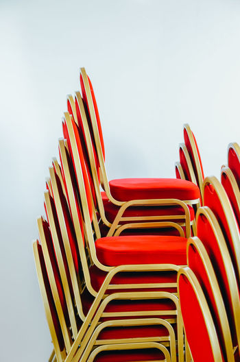 Red Chairs Stacked Against White Background