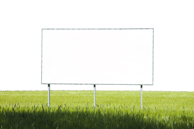 Blank advertising billboard Billboard Blank Blank Advertising Billboard Advertising Billboard Agriculture Billboard Blank Clear Sky Copy Space Day Empty Environment Field Grass Green Color Land Landscape Nature No People Outdoors Placard Plant Sky White Color
