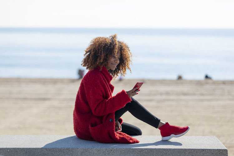 Side view of a young beautiful curly african american woman sitting on a bench at beach while using a mobile phone outdoors One Person Sitting Water Land Focus On Foreground Sea Full Length Beach Leisure Activity Women Curly Hair Nature Sky Hair Hairstyle Day Lifestyles Casual Clothing Real People Horizon Over Water Outdoors Young Adult Woman African American Afro Denim Happiness Happy Fun Daylight Sunlight