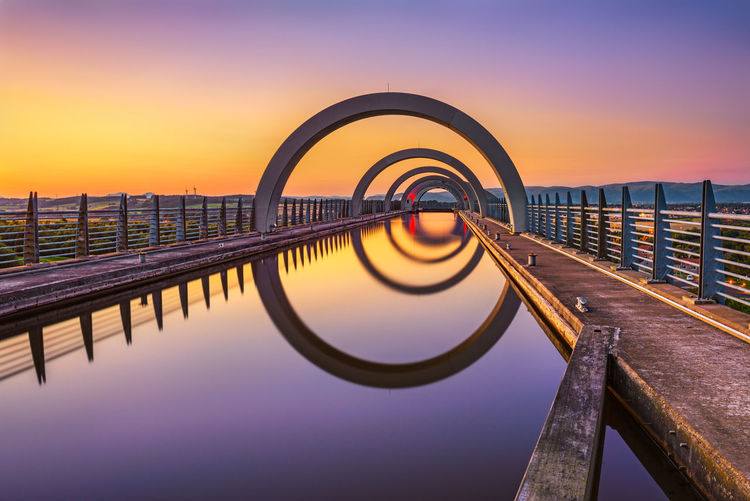 Reflection of pier on sea against sky during sunset
