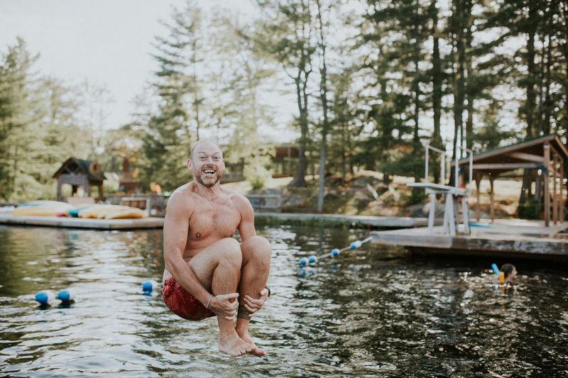 Full length portrait of shirtless man jumping in lake