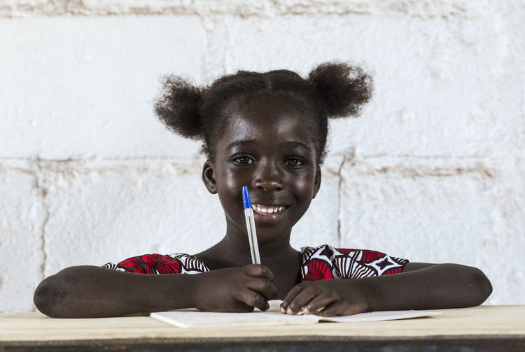 Portrait of smiling girl sitting against wall