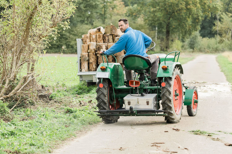 Rear view of man driving tractor at field