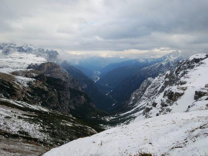 Scenic view of snowcapped tre cime di lavaredo against cloudy sky