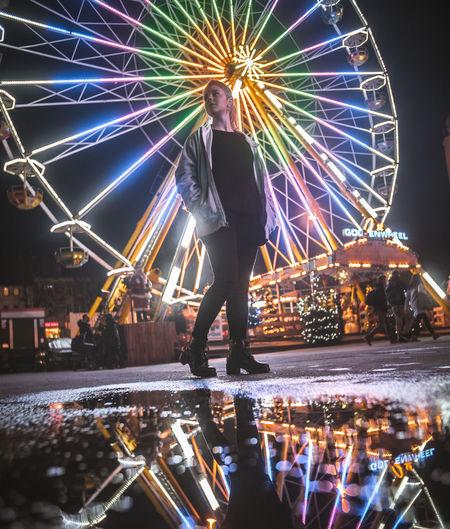 Woman Standing Against Illuminated Ferris Wheel At Night