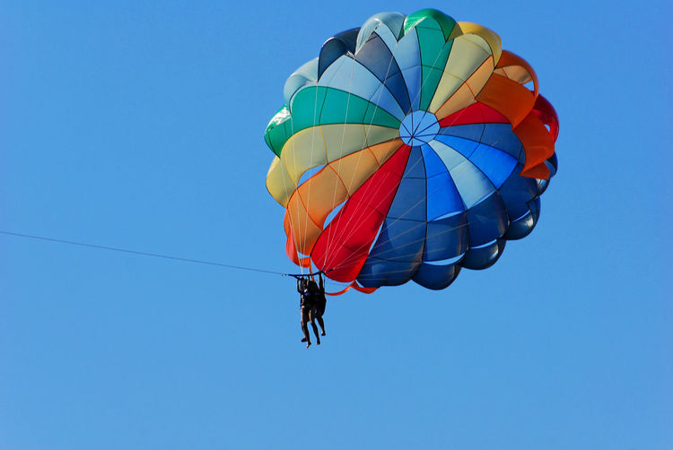 Low Angle View Of Parachute Against Clear Blue Sky