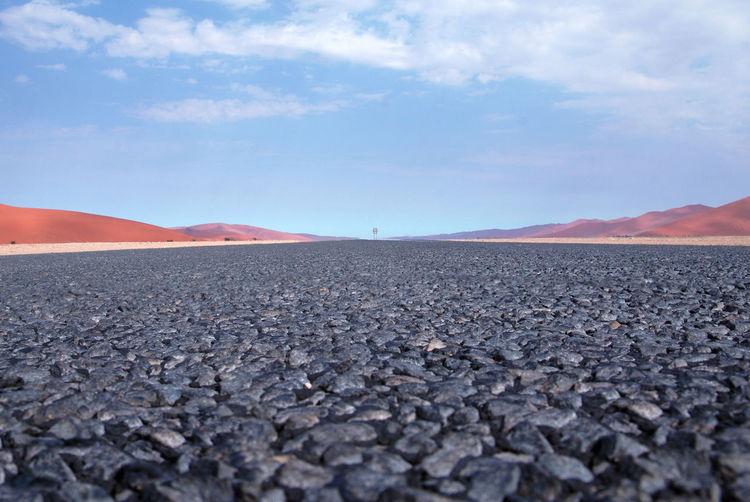 Surface level of barren landscape against sky