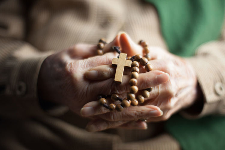 Close-Up Of Woman Holding Rosary With Hands Clasped