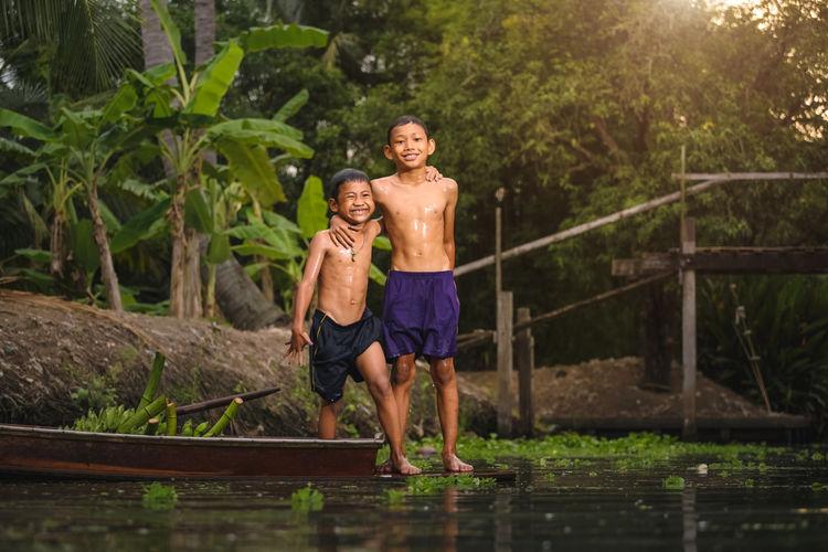 Full length portrait of shirtless boys standing on boat in river