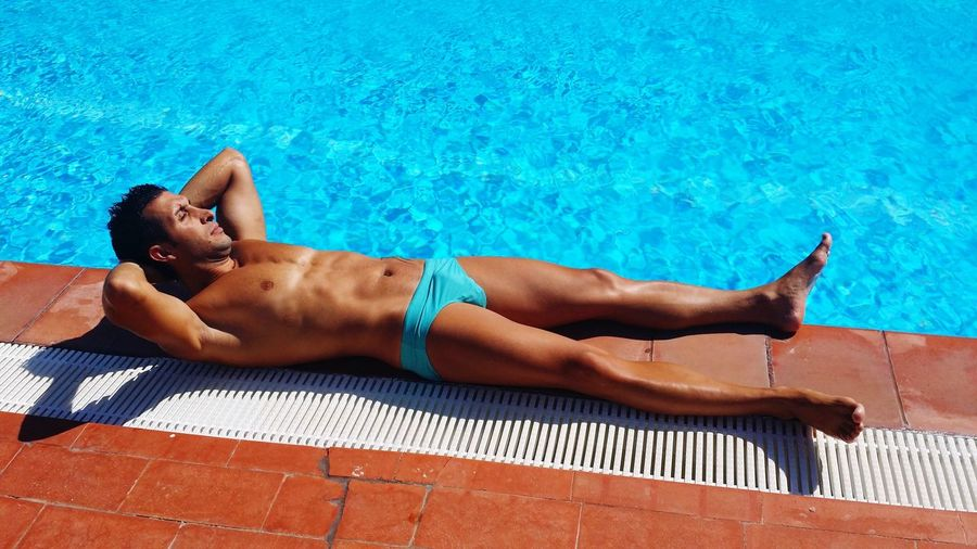 Mid Adult Lying By Swimming Pool