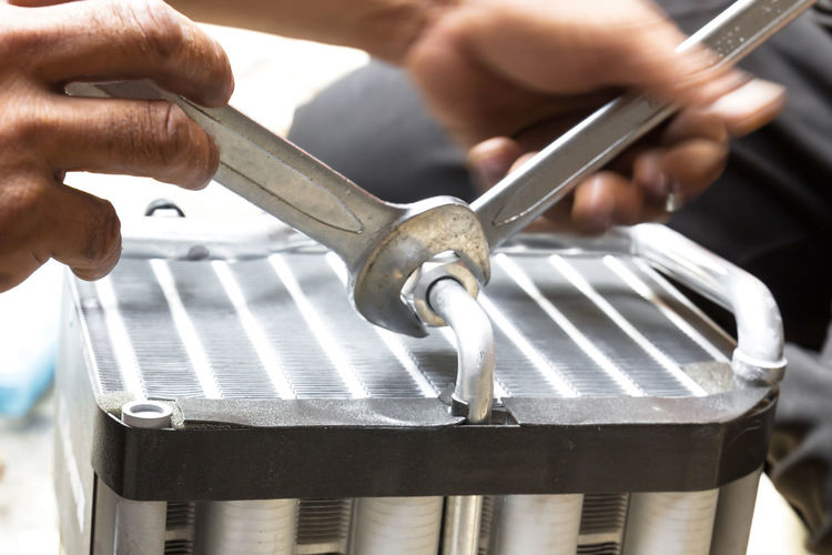 Cropped hands of electrician repairing machine in factory