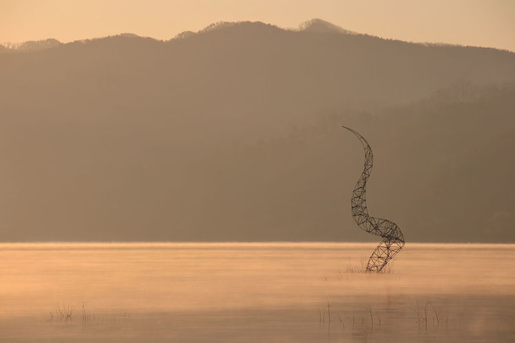 Metal sculpture in lake against silhouette mountain during sunset