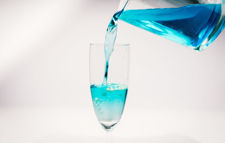 blue water in a glass Blue Water Clear Water Pure Blue Water Alcohol Drink Tirsty EyeEm Selects Water Liquid Motion Pouring Drop No People Science White Background Scientific Experiment Freshness Close-up