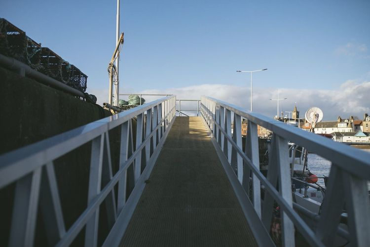 Footbridge over street in city against sky