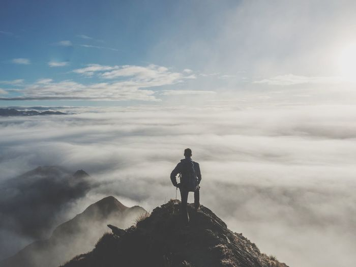 Rear view of young man with backpack standing on mountain against cloudy sky
