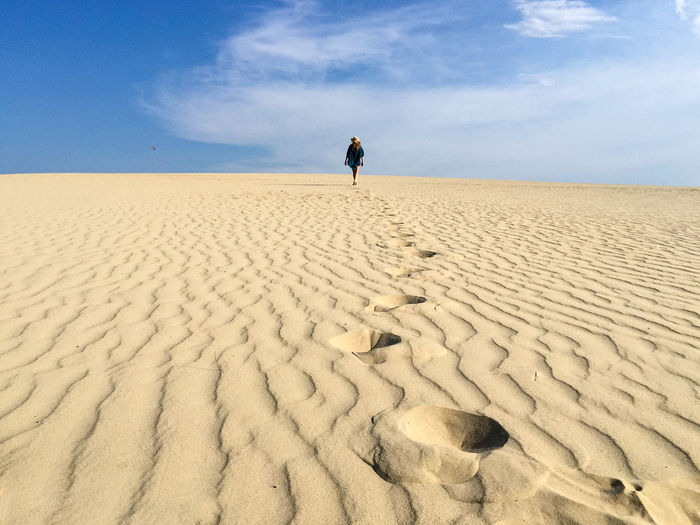 Woman walking on desert against sky