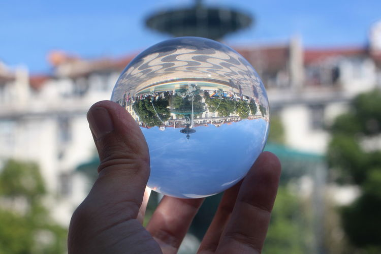 Close-up of hand holding crystal ball against building in city