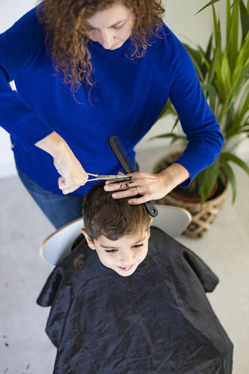 Funny boy getting haircut at home with scissors